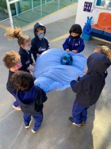 Alunos do Cermac Baby fazendo uma dinâmica baseada na confiança e respeito ao próximo, para evitar derrubar a bola no chão